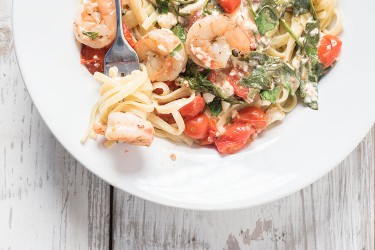 spicy shrimp pasta with feta cheese, spinach, and tomatoes