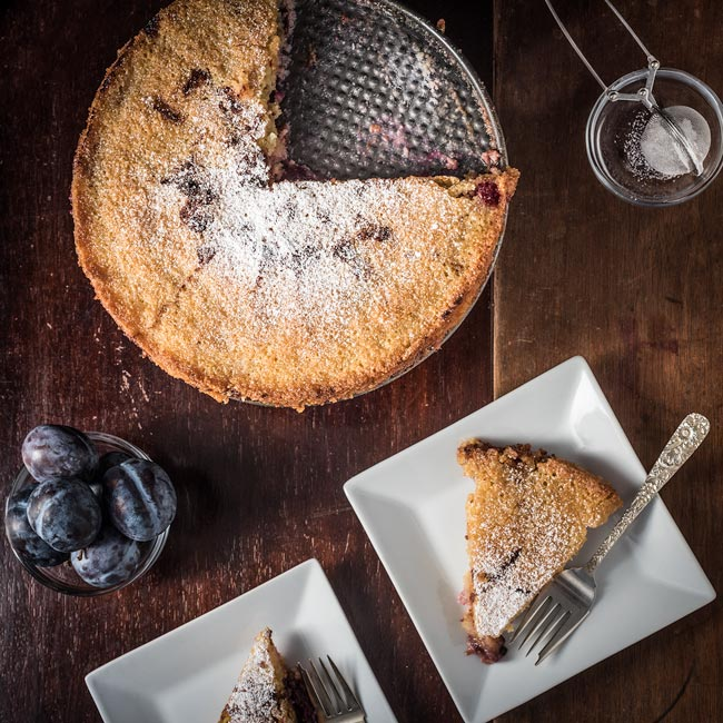 gluten-free plum torte dessert with powdered sugar