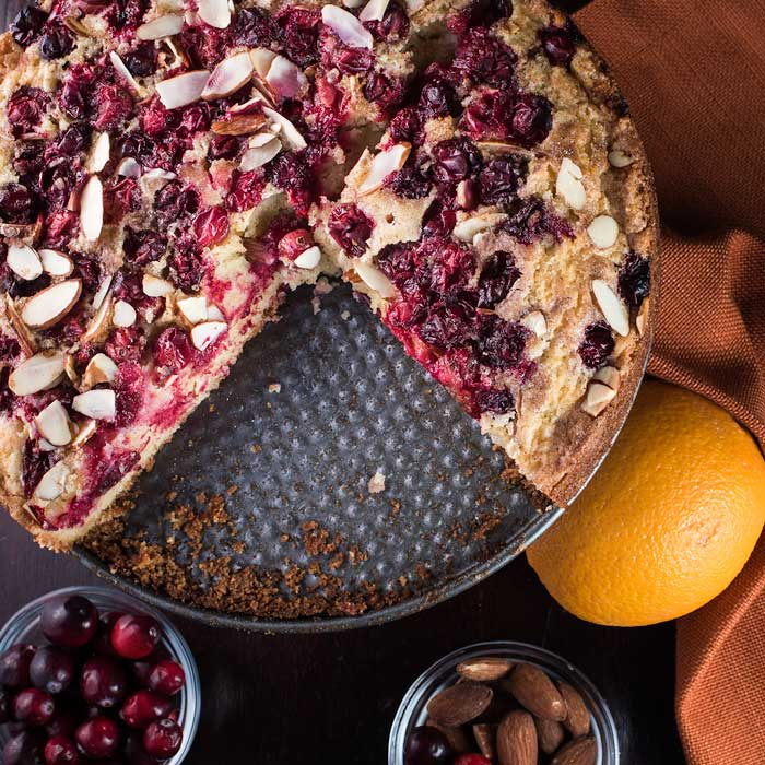 cranberry orange torte topped with almonds and orange drizzle
