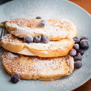 dairy-free french toast on plate served with powdered sugar and blueberries